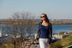 Muchacha elegante en gafas de sol con el pelo largo y una chaqueta de cuero fotografía de archivo
