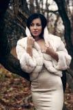 Muchacha elegante en la capa blanca con el alto collar Foto de archivo libre de regalías
