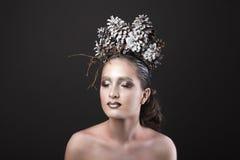 Muchacha elegante en la guirnalda del Año Nuevo de los conos del pino Imagen de archivo