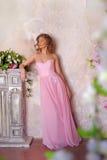 Muchacha elegante en un vestido de noche largo rosado foto de archivo