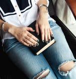 Muchacha elegante en vaqueros rasgados que lee un libro con una manicura verde hermosa y un reloj Moda, forma de vida, educación Imagen de archivo libre de regalías