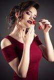 Muchacha elegante en vestido rojo con la cereza en manos Foto de archivo libre de regalías