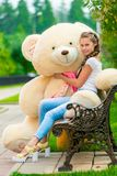 Muchacha elegante encantadora en un banco con un oso de peluche Fotografía de archivo