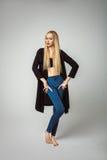 Muchacha elegante hermosa en la presentación de los vaqueros del dril de algodón de la moda Fotos de archivo libres de regalías