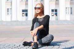 Muchacha elegante hermosa en una camiseta negra, vaqueros y sitti de los zapatos Fotografía de archivo