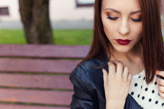 Muchacha elegante hermosa en una chaqueta de cuero negra con el lápiz labial oscuro y maquillaje en la ciudad en el banco Imagen de archivo libre de regalías