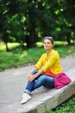 Muchacha elegante hermosa joven con el bolso en un parque del verano Imagen de archivo