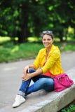 Muchacha elegante hermosa joven con el bolso en un parque del verano Fotografía de archivo libre de regalías