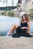 Muchacha elegante hermosa que descansa sobre la orilla del lago Imágenes de archivo libres de regalías
