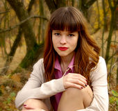 Muchacha elegante hermosa que se coloca en un parque en otoño Imagenes de archivo