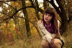 Muchacha elegante hermosa que se coloca en un parque en otoño Imágenes de archivo libres de regalías