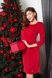 Muchacha elegante hermosa vestida en actitudes rojas del vestido con la caja roja en sus manos al lado del árbol del Año Nuevo imágenes de archivo libres de regalías