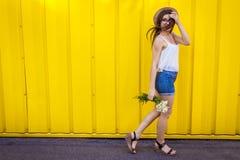 Muchacha elegante joven en vidrios y sombrero que camina en ciudad y que sostiene las flores contra fondo amarillo Equipo del ver Foto de archivo libre de regalías