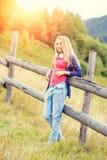 Muchacha elegante joven que coloca la cerca cercana en ladera Imagen de archivo