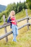 Muchacha elegante joven que coloca la cerca cercana en ladera Fotos de archivo libres de regalías