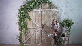 Muchacha elegante joven que presenta contra la puerta de madera, sonriendo y mirando la cámara almacen de video
