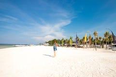Muchacha elegante linda en el vestido azul que se coloca en la playa asombrosa con la arena del wite, sosteniendo smartphone en s Imagenes de archivo