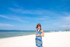 Muchacha elegante linda en el vestido azul que se coloca en la playa asombrosa con la arena del wite, sosteniendo smartphone en s Fotos de archivo libres de regalías