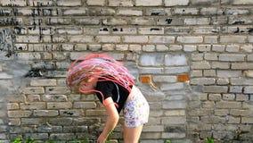 Muchacha elegante que agita las coletas africanas cerca de una pared de ladrillo - cámara lenta metrajes