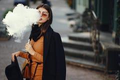 Muchacha elegante que fuma un e-cigarrillo Imagen de archivo