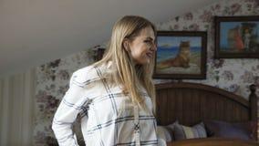 Muchacha elegante que presenta con sonrisa en dormitorio cómodo ligero 4K almacen de metraje de vídeo