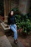 Muchacha elegante que se coloca cerca del kolum griego en un jardín de flores Fotografía de archivo