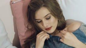 Muchacha elegante que se relaja, mintiendo y presentando en la cama lentamente almacen de video