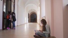 Muchacha elegante que se sienta en piso y el libro de lectura durante rotura metrajes