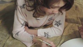 Muchacha elegante que soluciona ecuaciones matemáticas en la cama, enseñando en casa la educación almacen de video