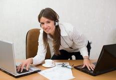 Muchacha elegante rápida en el escritorio de oficina con las computadoras portátiles Imagenes de archivo