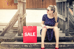 Muchacha elegante y atractiva que se sienta en un puente de madera, cerca de un bolso rojo Imagen de archivo libre de regalías