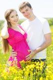 Muchacha embarazada con el marido en campo de flores Fotos de archivo