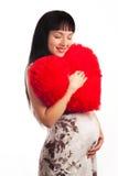 Muchacha embarazada de los jóvenes que abraza un corazón grande suave Imagen de archivo