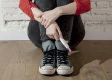 Muchacha embarazada del adolescente o mujer desesperada joven que lleva a cabo la prueba de embarazo rosada positiva Imagen de archivo libre de regalías