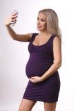 Muchacha embarazada en un vestido que toma el selfie Cierre para arriba Fondo blanco Foto de archivo libre de regalías