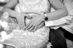 Muchacha embarazada en vestido, sus manos, y mano del ` s del marido en su estómago en la forma de corazón Fotos de archivo libres de regalías