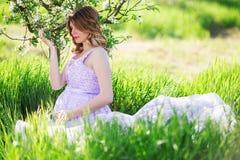 Muchacha embarazada feliz en jardín de la primavera del flor Foto de archivo libre de regalías