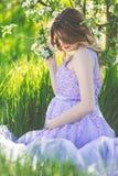 Muchacha embarazada feliz en jardín de la primavera del flor Fotos de archivo libres de regalías