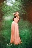 Muchacha embarazada hermosa joven con el pelo marrón largo en vestido del melocotón en jardín verde Imagen de archivo libre de regalías