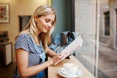 Muchacha embarazada joven hermosa que se sienta en la revista a de la lectura del café foto de archivo