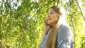 Muchacha embarazada Mujer embarazada en parque Mujer que habla en el teléfono almacen de metraje de vídeo