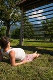 Muchacha embarazada que descansa sobre hierba Imagenes de archivo