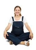 Muchacha embarazada que hace yoga Imagenes de archivo