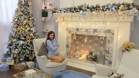Muchacha embarazada que se sienta en silla cerca del árbol de navidad almacen de video
