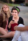 Muchacha embarrassed con el teléfono Imagenes de archivo