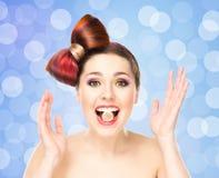 Muchacha emocionada atractiva con el pelo coloreado con el caramelo en boca Foto de archivo