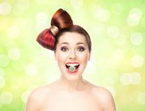 Muchacha emocionada atractiva con el pelo coloreado que come el caramelo en boca Foto de archivo