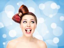 Muchacha emocionada atractiva con el pelo coloreado que come el caramelo en boca en fondo burbujeante Imágenes de archivo libres de regalías
