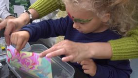 Muchacha emocionada de la hija con la madre hacer la pintura del ebru en el agua Movimiento del cardán almacen de video