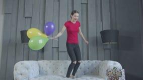 Muchacha emocionada del cumpleaños que salta en el sofá en casa metrajes
